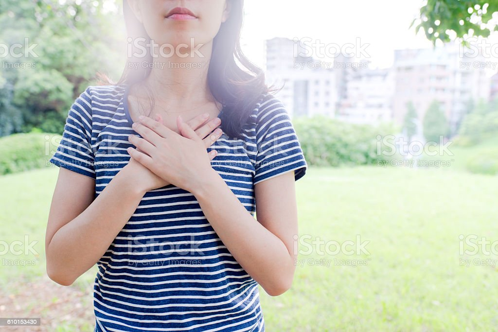 Woman holding her chest stock photo