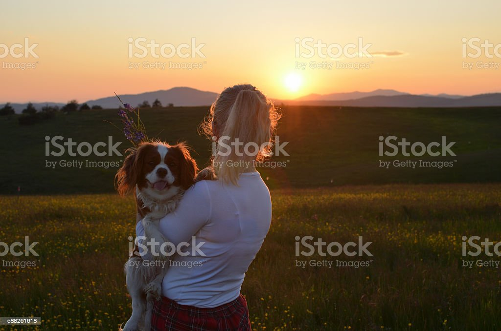 Woman Holding Her Dog in Sunset stock photo