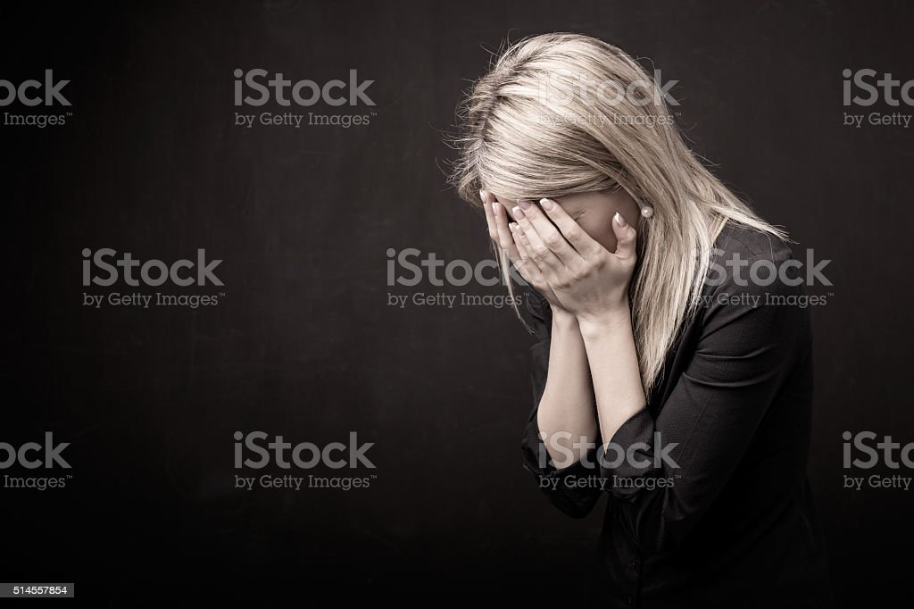 Woman holding her face in her hands stock photo