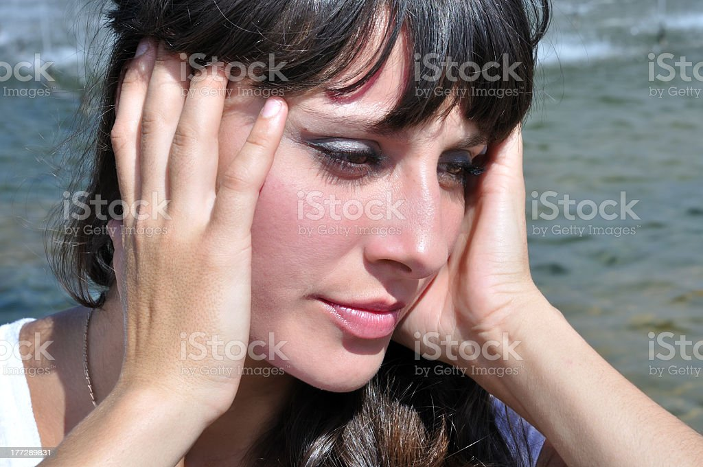 A woman holding her head at the beach, suffering heatstroke stock photo