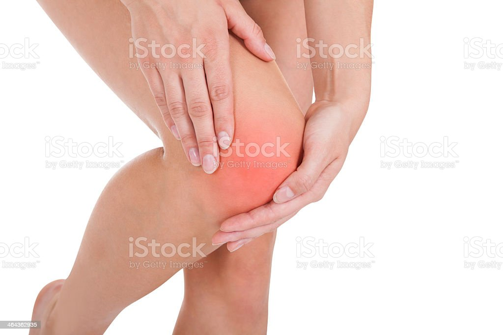 Woman holding her inflamed knee in pain stock photo