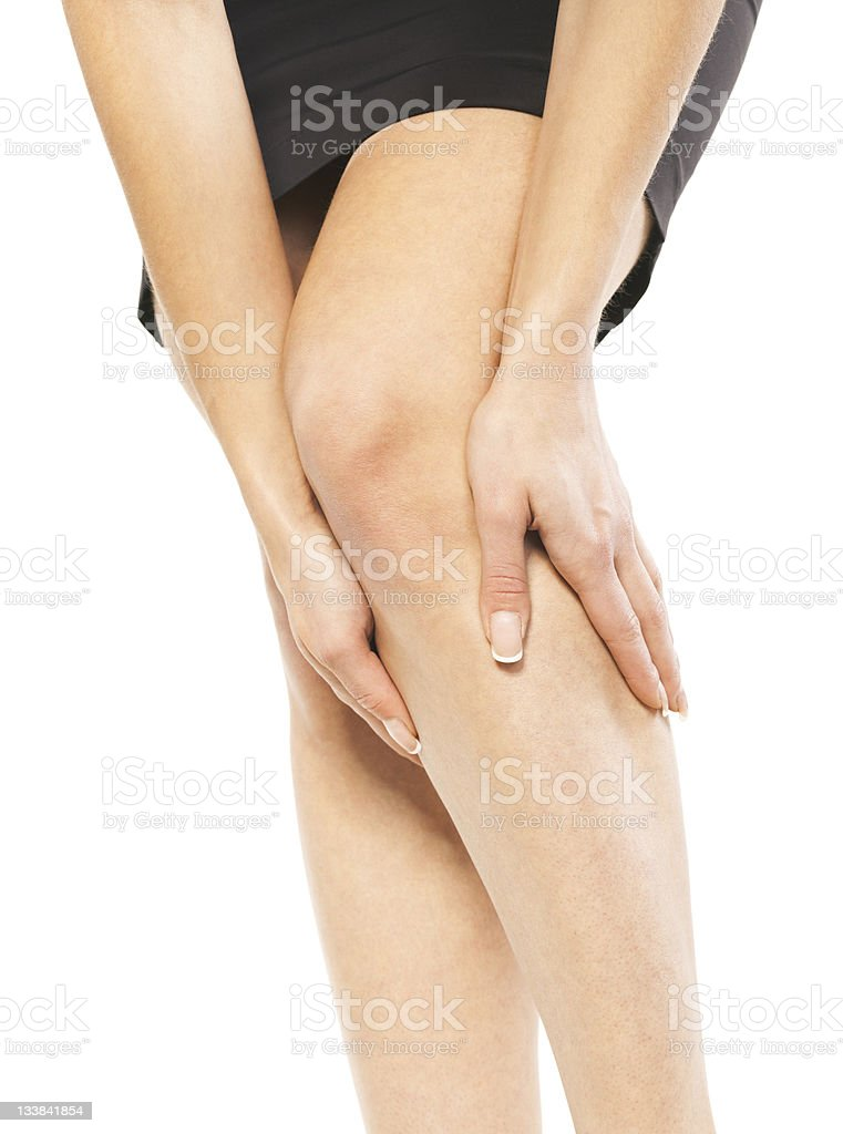 A woman holding her knee in pain stock photo