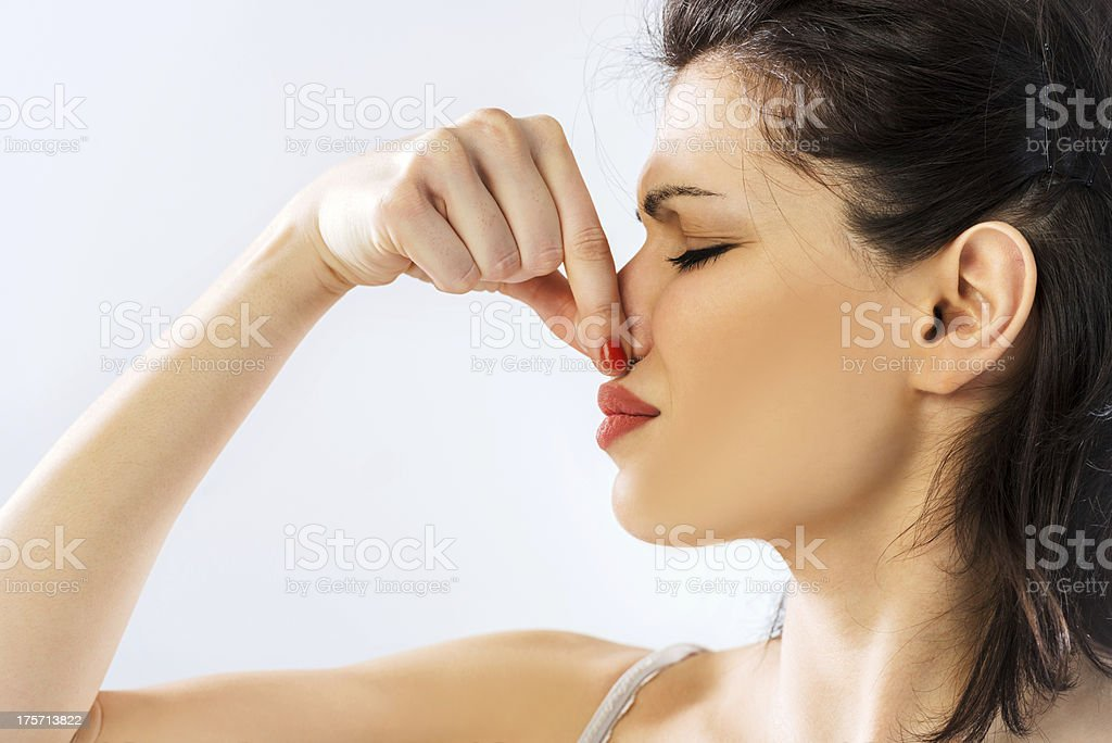 Woman holding her nose. stock photo