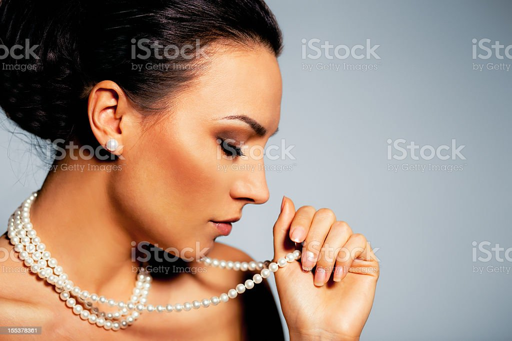 A woman holding her pearl necklace royalty-free stock photo