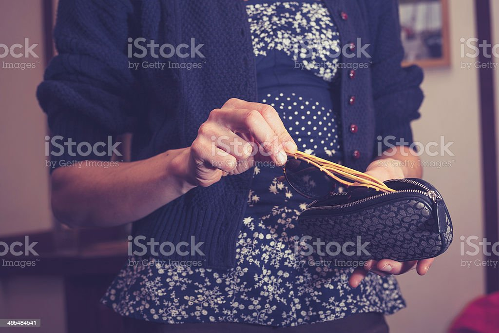 Woman holding her sunglasses stock photo