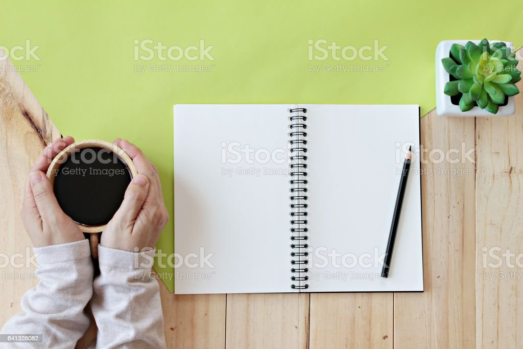 Woman holding hot cup of coffee with blank notebook and pencil stock photo
