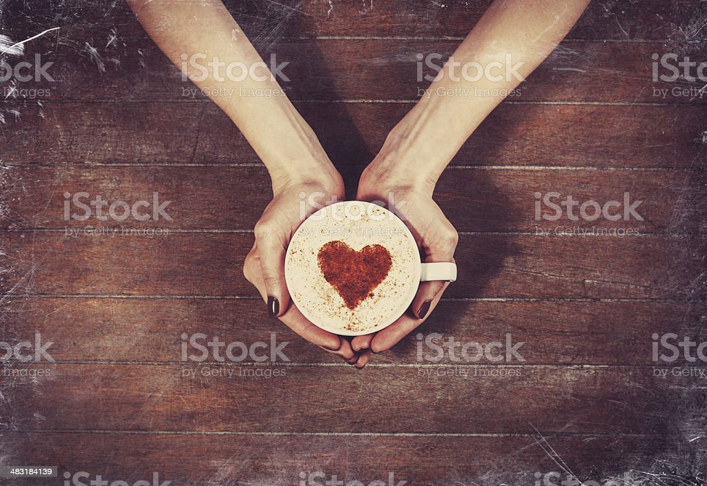 woman holding hot cup of coffee, with heart shape stock photo