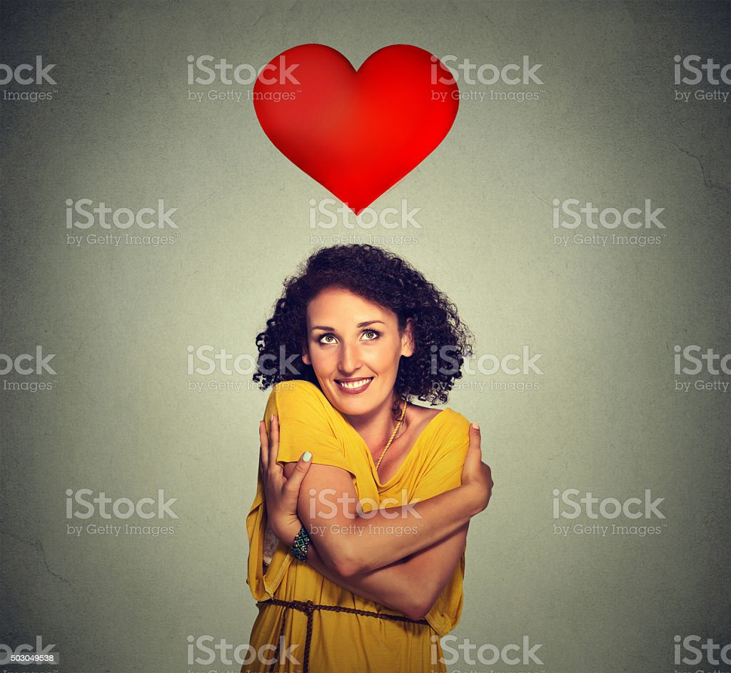 woman holding hugging herself with red heart above head stock photo