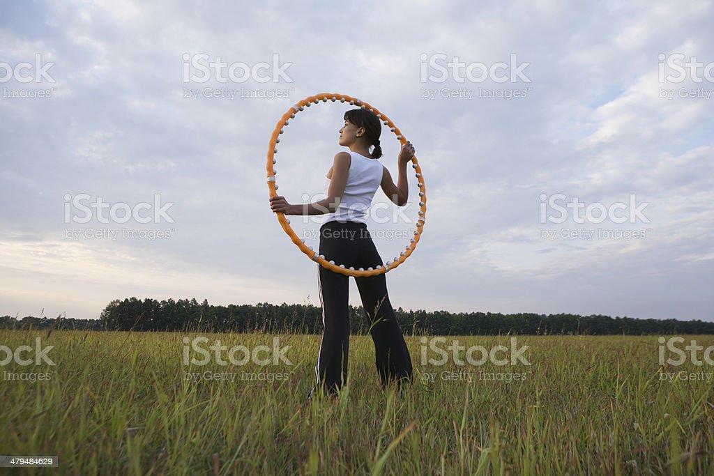 Woman Holding Hula Hoop On Field stock photo