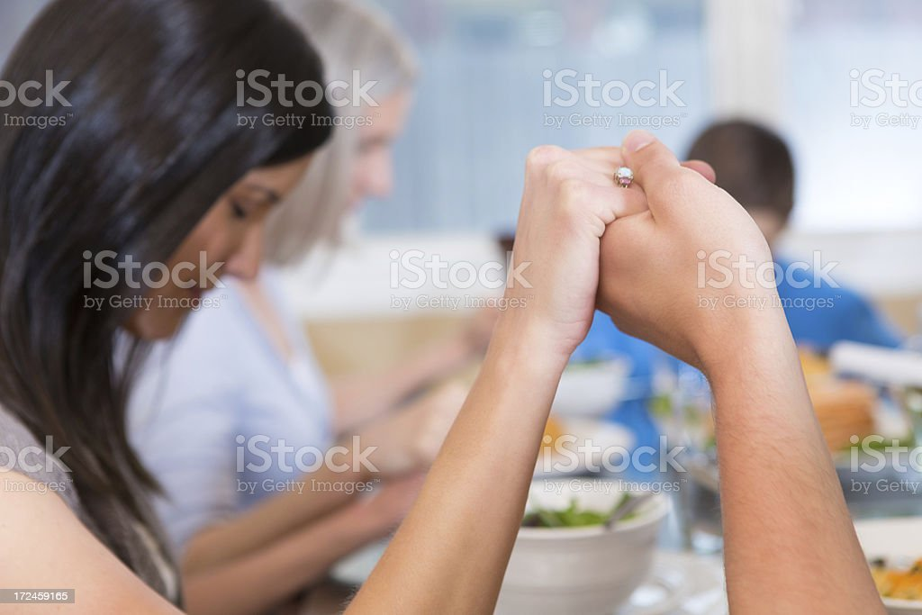 Woman holding husband's hand while praying before a family meal stock photo