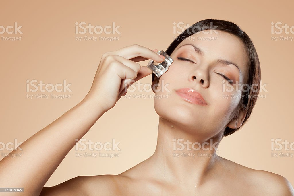 woman holding ice cube on her face stock photo
