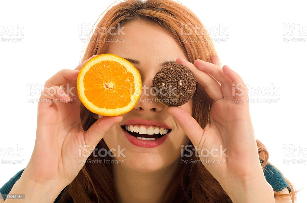 Woman holding in front of her eyes orange and candy. stock photo