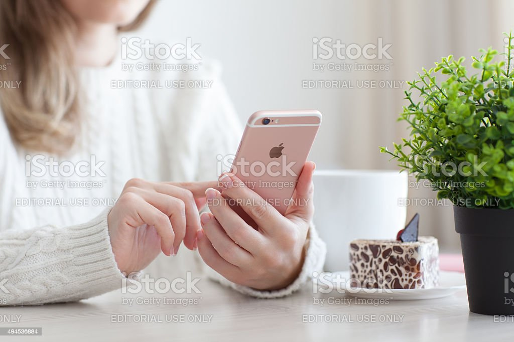 Woman holding iPhone 6 S Rose Gold in cafe stock photo