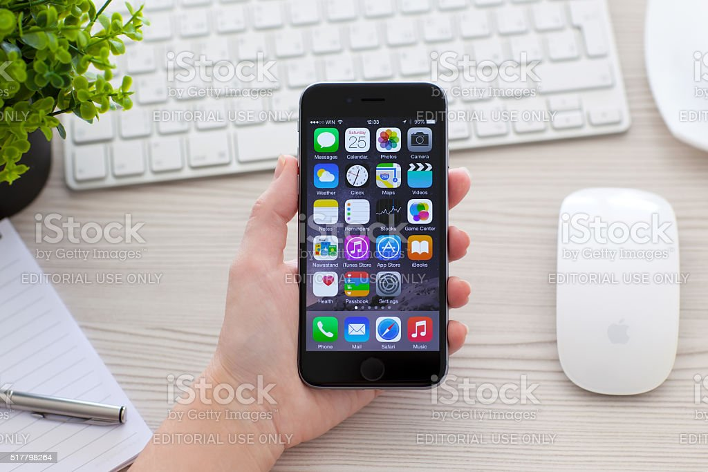 Woman holding iPhone 6 Space Gray over the table stock photo