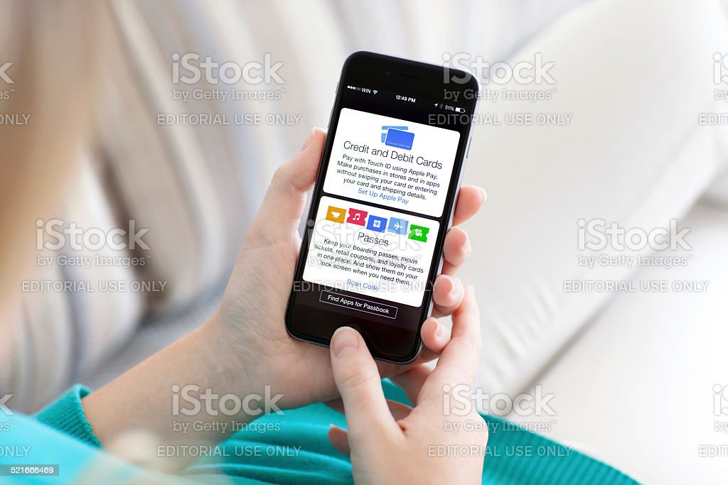 Woman holding iPhone 6 with Apple Pay and Passbook stock photo