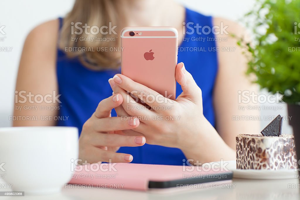 Woman holding iPhone6S Rose Gold in cafe stock photo