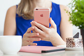 Woman holding iPhone6S Rose Gold in cafe