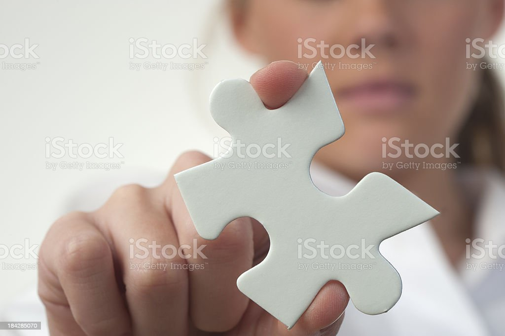 Woman holding jigsaw puzzle piece royalty-free stock photo