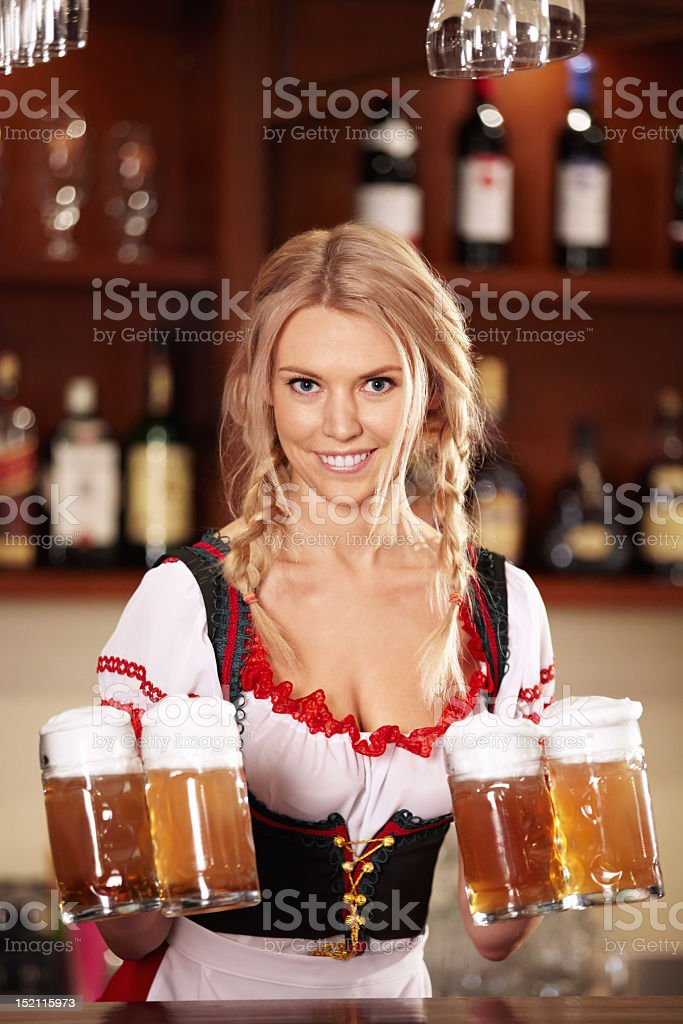 A woman holding jugs of beer at the bar stock photo