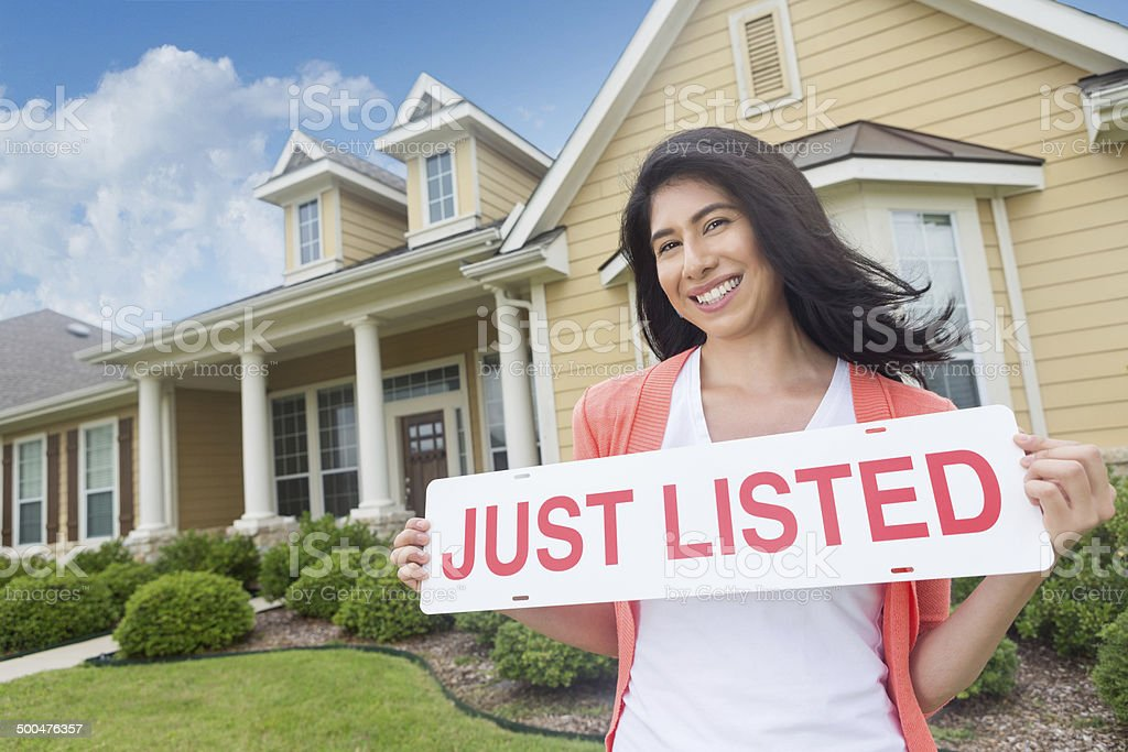 Woman holding 'just listed' sign in front of beautiful home stock photo