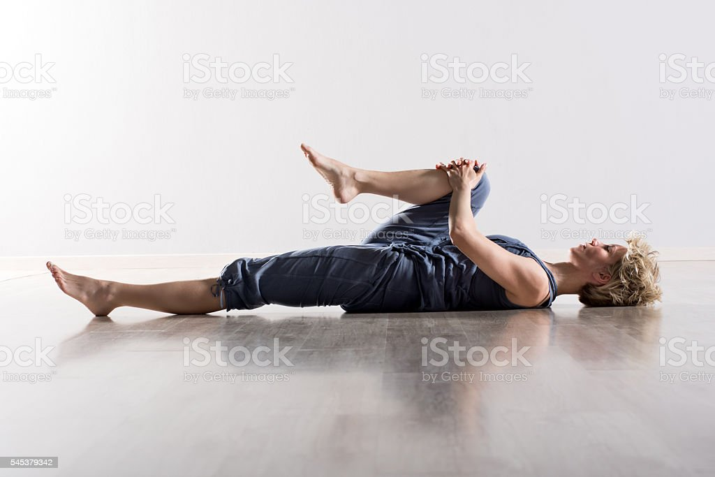 Woman holding knee while stretching hamstring stock photo