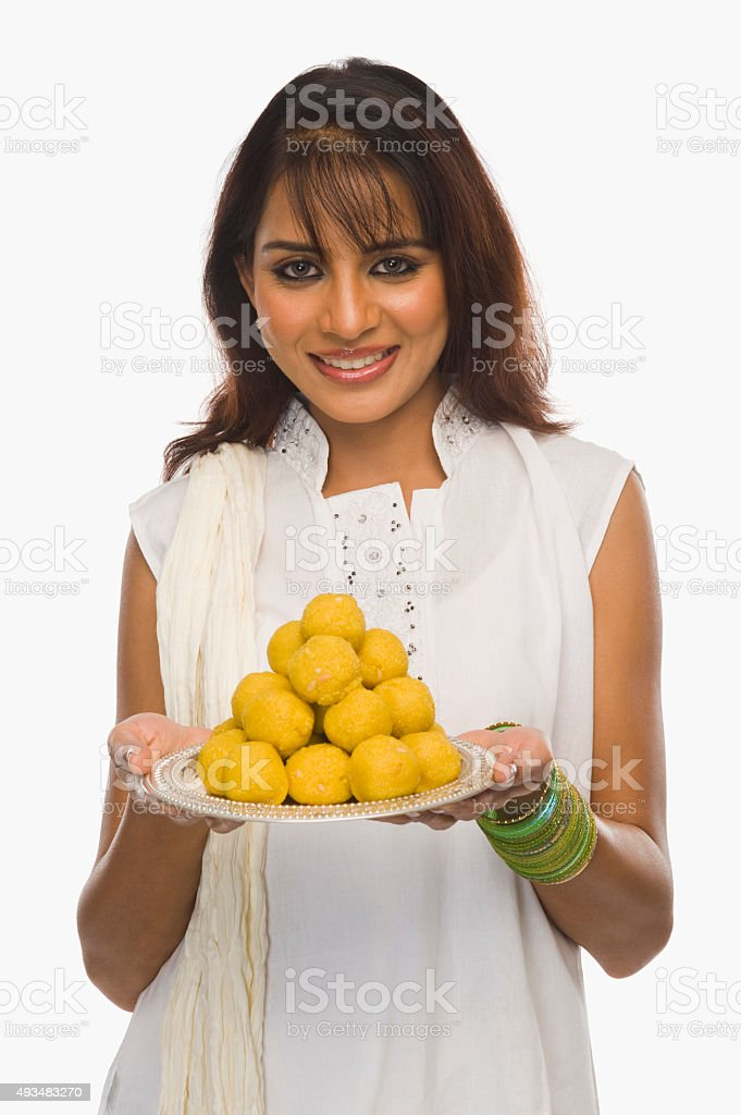 Woman holding Laddu in a plate on Holi stock photo