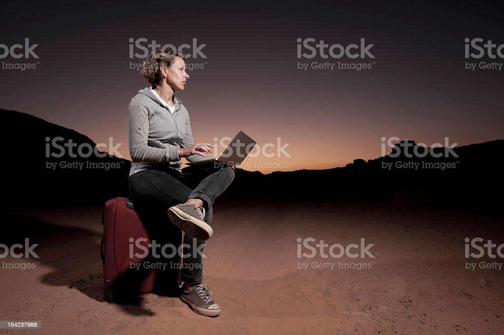 Woman holding laptop in desert at night royalty-free stock photo