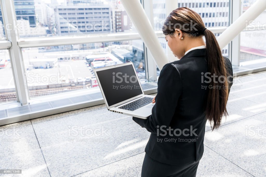 woman holding laptop in office building stock photo