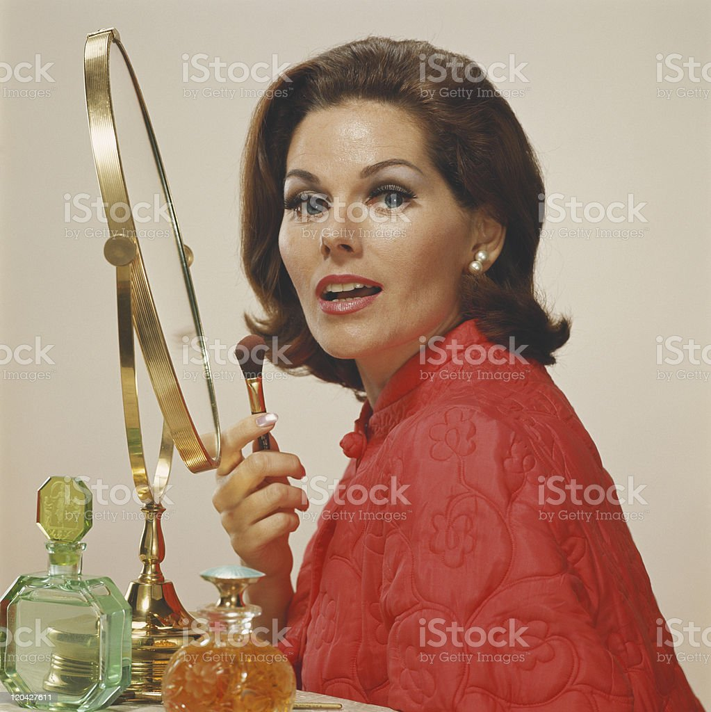 Woman holding makeup brush, portrait stock photo