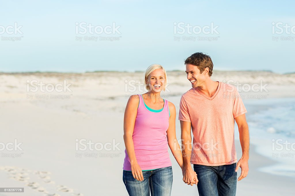 Woman Holding Man's Hand While Walking On Beach stock photo