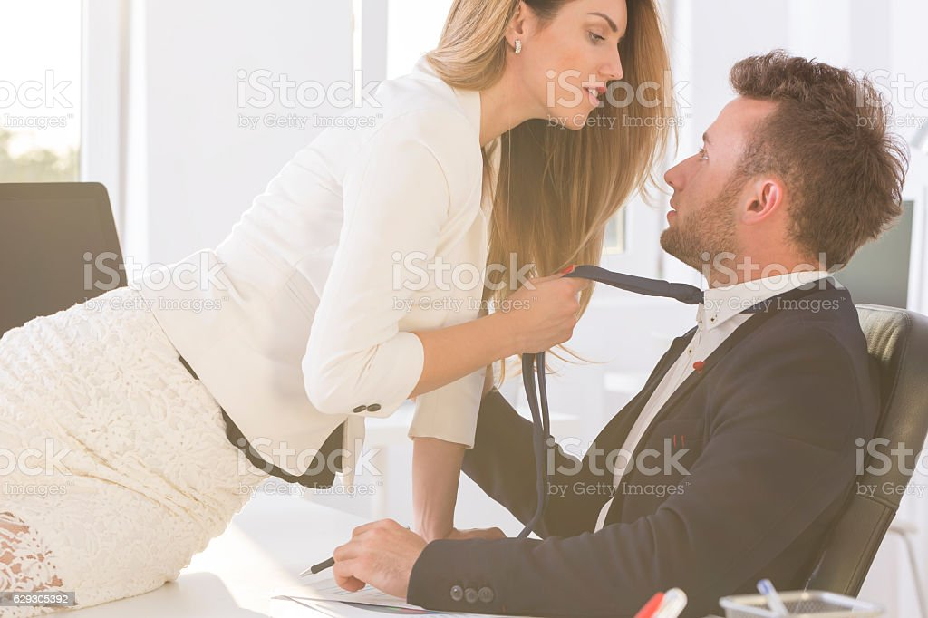 Woman  holding man's tie in the office stock photo