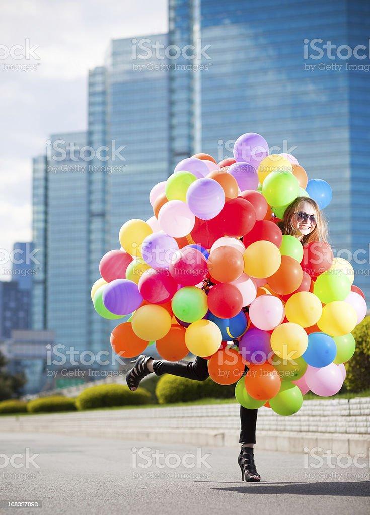 Woman holding many balloons stock photo