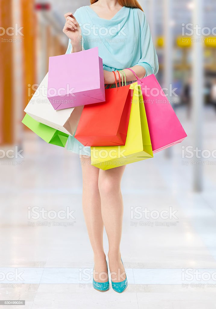 Woman holding many shopping bags in shopping mall stock photo