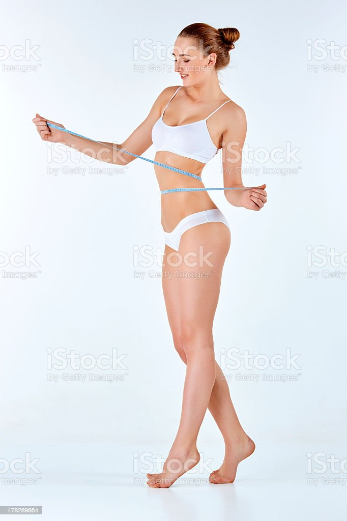 Woman holding meter measuring perfect shape of her beautiful body stock photo