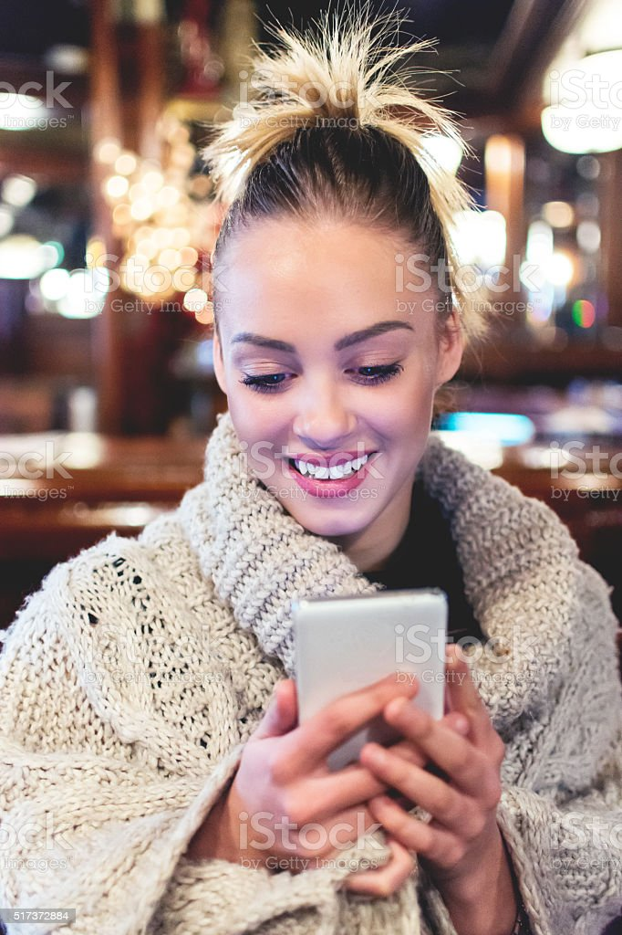 Woman holding mobile phone in a cafe stock photo