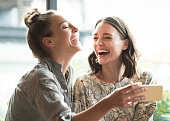 Woman holding mobile phone with freind, laughing