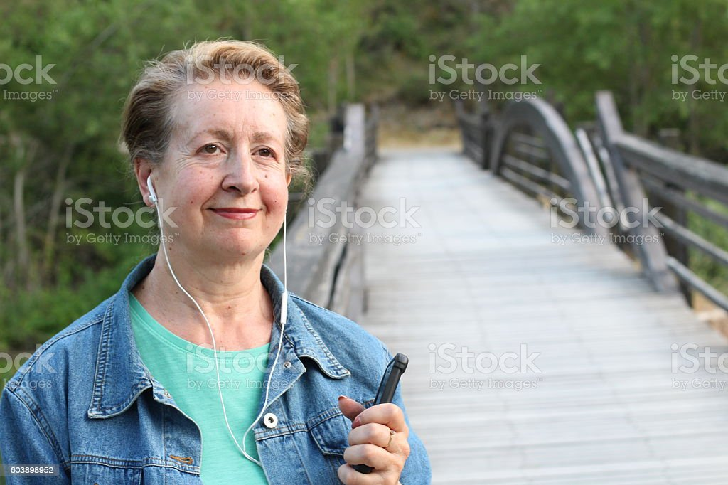 Woman holding mobile phone with headphones stock photo