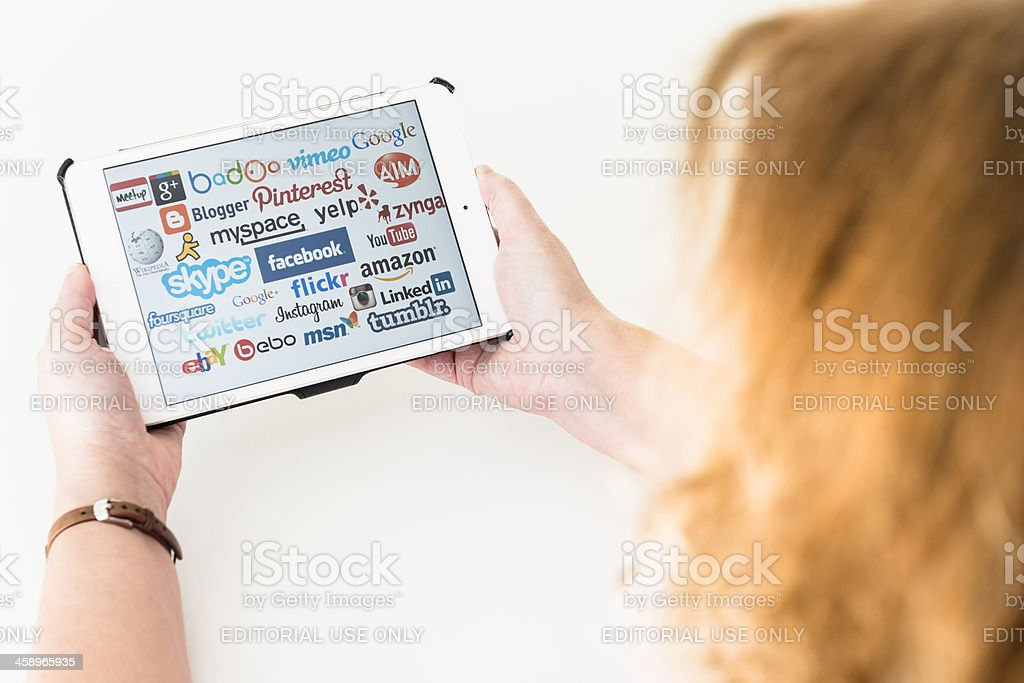 Woman holding new Ipad mini with some social media website royalty-free stock photo