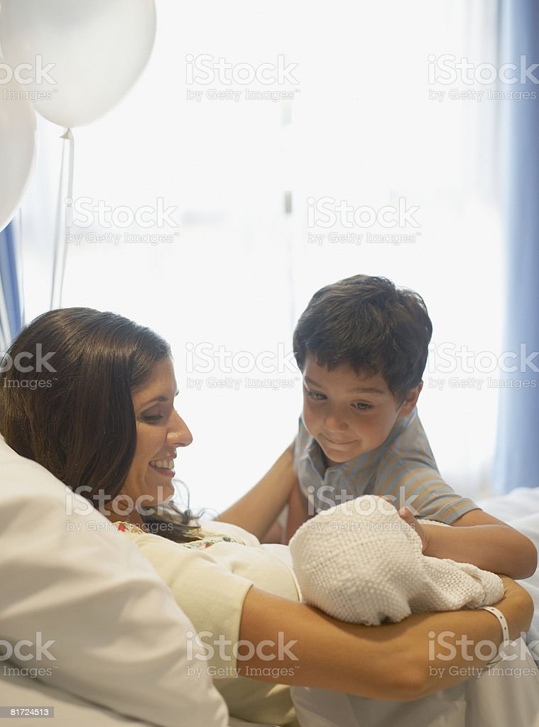 Woman holding newborn baby in hospital bed smiling while young boy watches over royalty-free stock photo