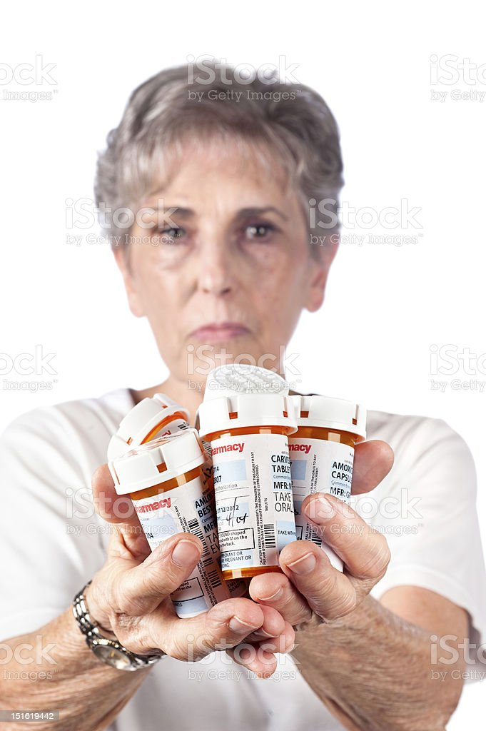 Woman holding out several prescription bottles and frowning stock photo