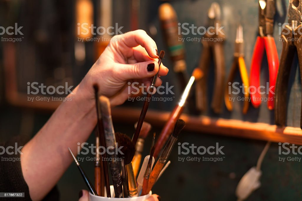 woman holding paintbrushes stock photo