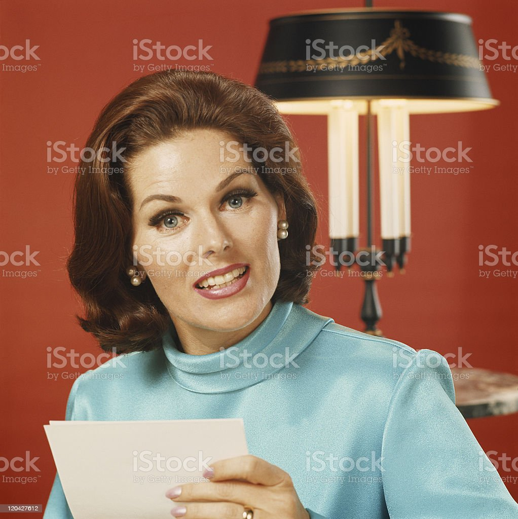 Woman holding paper, portrait, close-up stock photo