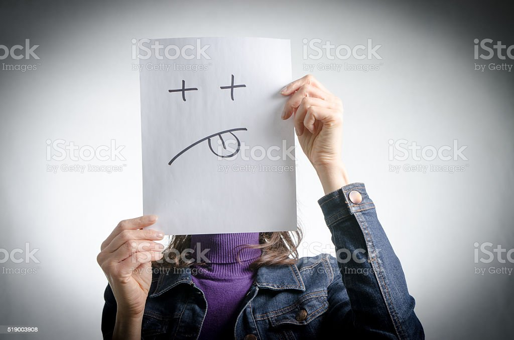 Woman holding paper with sad face in front of head stock photo