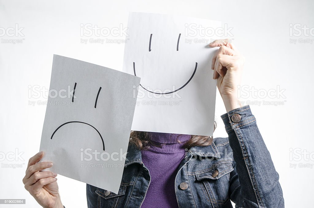 Woman holding paper with smiley and sad face stock photo