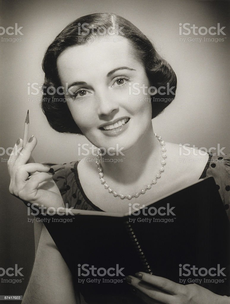 Woman holding pencil and notebook, posing in studio, (B&W), (Close-up), (Portrait) royalty-free stock photo