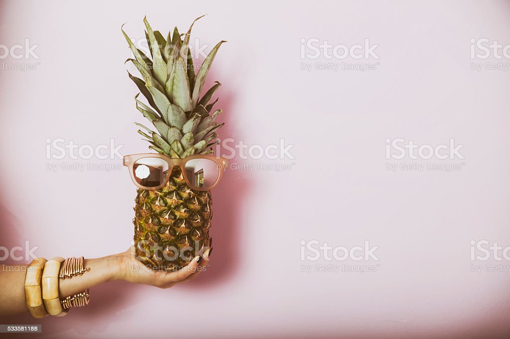 Woman holding pineapple with glasses. Summer concept image. stock photo