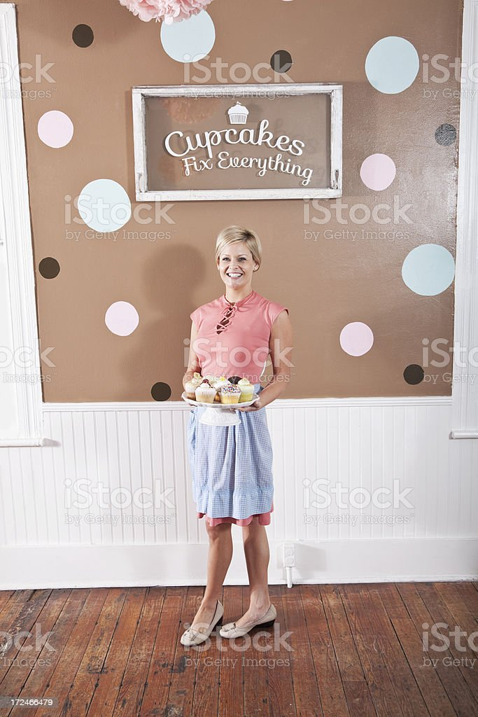 Woman holding plate of cupcakes stock photo