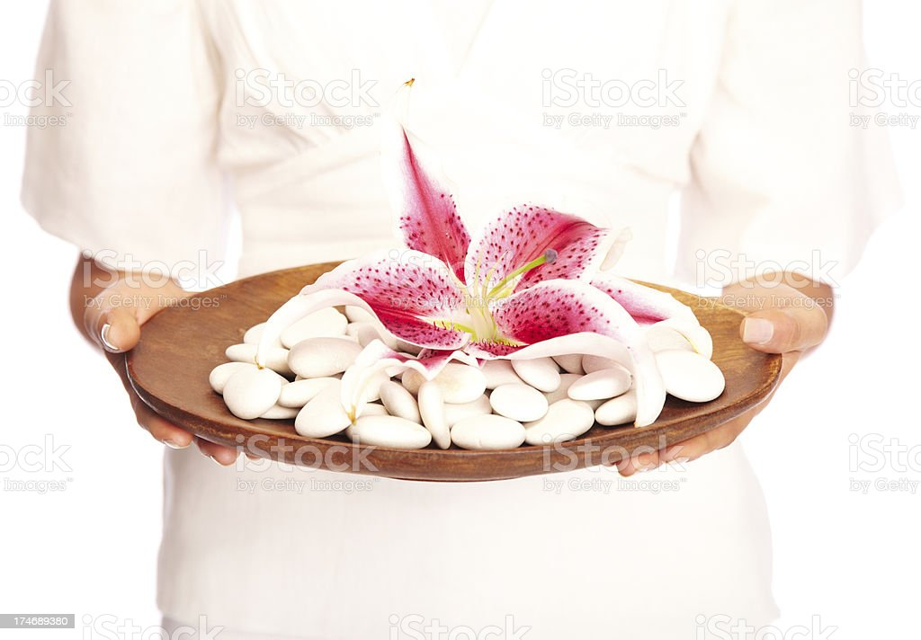 Woman holding plate of spa stones and a stargazer lily stock photo
