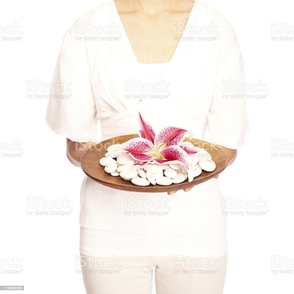 Woman Holding Plate of white Spa Stones & Stargazer Lilies stock photo
