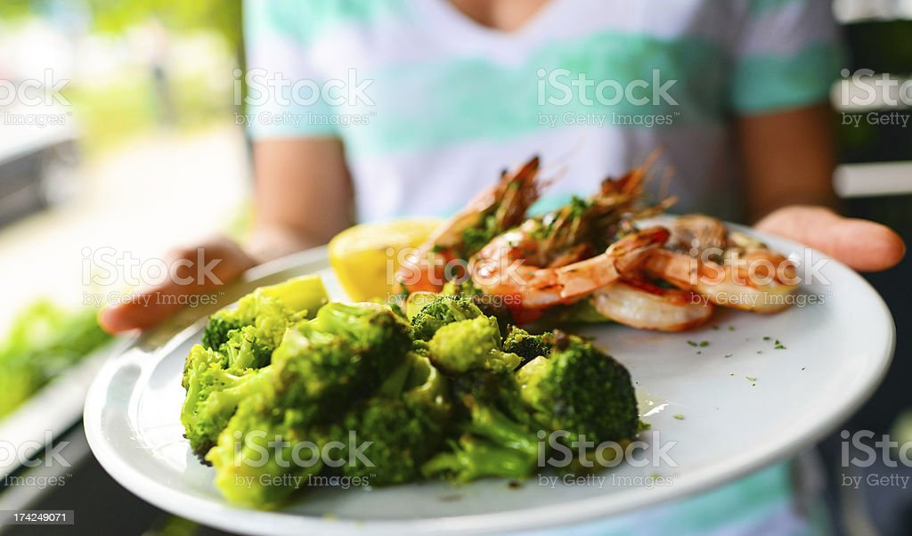 Woman holding plate with grilled king prawns and broccoli royalty-free stock photo